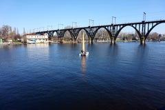 Spławowa żaglówka na tle kolejowy most przez rzekę fotografia royalty free