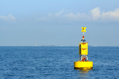 Spławowy żółty nawigacyjny boja na błękitnym morzu obrazy stock
