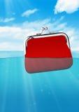 Spławowy czerwony portfel przy oceanem, kolorowy finansowy pojęcie Zdjęcia Stock