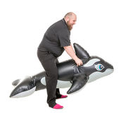 Spaß des dicken Mannes, der auf einen aufblasbaren Delphin springt Stockfotografie