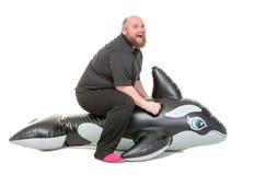 Spaß des dicken Mannes, der auf einen aufblasbaren Delphin springt Lizenzfreie Stockfotos