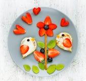 Spaß mit Lebensmittel - Erdbeerkiwi-Blaubeervögel auf Blume lizenzfreie stockfotos