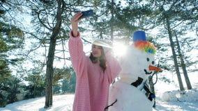 Spaß selfie Foto im Winterwald hintergrundbeleuchtet, nettes Mädchen, das in der Hand Foto mit einem Schneemann, Winter selfie, H stock video