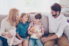Spaß-Zeit zusammen Glückliche vierköpfige Familie hört auf kleines BO Stockbild
