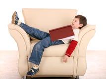 Spaßjungenschlaf mit Buch. Lizenzfreies Stockfoto