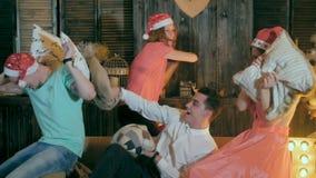 Spaßkissenschlacht Gruppe Freunde, die Spaß, Weihnachtsfest zusammen genießend haben und spielen mit den Kissen und lachen stock video footage