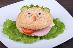 Spaßlebensmittel für Kinder - Hamburger sieht wie eine lustige Mündung aus Stockbild