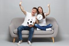 Spaßpaarfrauen-Mannfußballfane jubeln oben Stützlieblingsteam mit Fußball zu und halten die runde Uhr und zeigen Daumen lizenzfreies stockfoto
