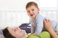 Spaßzeit: Freudige Mutter und Sohn, die im Bett spielt. Lizenzfreies Stockfoto
