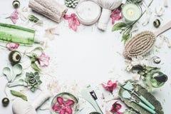 SPA και υπόβαθρο wellness με τα λουλούδια, τα καλλυντικά προϊόντα δερμάτων και άλλα προσοχή σωμάτων και εξαρτήματα μασάζ στο άσπρ στοκ φωτογραφίες