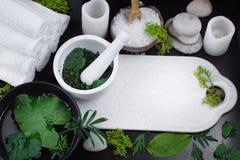 SPA που τίθεται με τις πετσέτες, τις πέτρες και τα άσπρα ηλεκτρικά κεριά που περιβάλλονται από τα πράσινα φύλλα των φυτών στοκ φωτογραφία