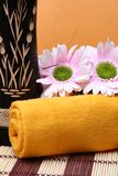 Spa. Flowers and yellow towel on a resort Royalty Free Stock Photos