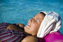 Spa. Woman wearing white towel and flower in pool Stock Images