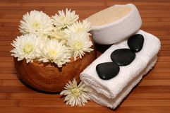 Spa. Towels, chrysanthemum, pebbles and bath sponge on a bamboo mat Royalty Free Stock Photography
