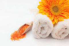 SPA still life with sea salt, towels and flower. SPA still life with sea salt, white towels and flower on clear white table background stock image