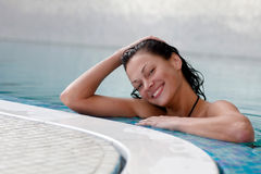 Spa. Smiling female at the edge of a swimming pool Royalty Free Stock Image