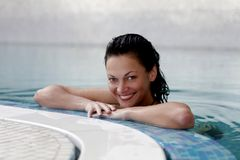 Spa. Smiling female at the edge of a swimming pool Stock Photo