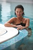 Spa. Smiling female at the edge of a swimming pool Royalty Free Stock Photo
