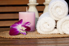 Spa. White towels with a candle and a flower on a teak table Royalty Free Stock Photos