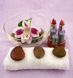 Spa. A spa set-up including lipstick, nail polish, white towel, stones and a bowl of water Royalty Free Stock Photo