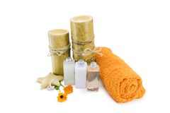 Spa. Setting with bamboo candles and orange accents over white background Royalty Free Stock Photo
