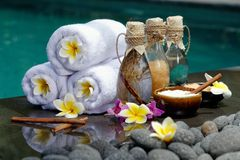 At the Spa. Concept in a luxury Villa on Bali Island with, Massage oil, bath-salt, Volcanic stones, body scrub, Towels,Cinnamon sticks, Orchids and flowers Royalty Free Stock Photo