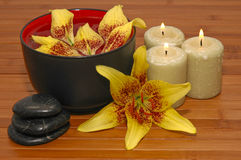 Spa. Scene with aromatic candles, healing pebbles, and fragrant flowers Royalty Free Stock Images