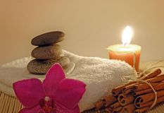 Spa. Pebble stones on white towel with orchid flower, candle and cinamon Royalty Free Stock Image