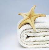Spa. Starfish on white towel on blue background Stock Photos