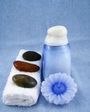 Spa. A spa still life on a blue background consisting of a towel with some stones on top, a blue candle and a bottle of lotion Royalty Free Stock Images