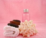 Spa. A spa still life against a pink background consisting of a towel with stones on top, a bottle of lotion and a shell Stock Photo