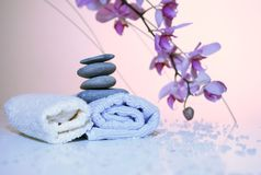 SPA accessories. Towels, stones,perfumed salt with tender orchids around Royalty Free Stock Image