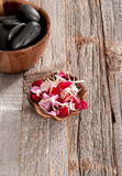 Spa accessories: hot stones for massage and flowers Stock Photos