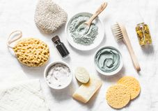 Spa accessories - nut scrub, sponge, facial brush, natural soap, clay face mask, pumice stone, essential oil on a light background Royalty Free Stock Images
