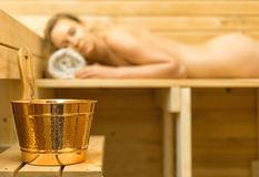 Spa accessories in sauna. Woman on background Royalty Free Stock Photo