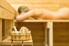 Spa accessories in sauna. Woman on background Stock Photography