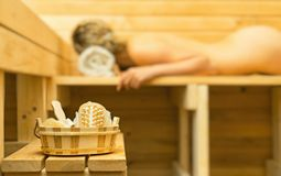 Spa accessories in sauna. Woman on background Stock Image