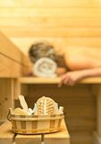 Spa accessories in sauna. Woman on background Stock Photos