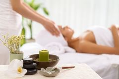 Spa accessories. And a woman receiving spa treatment in the background Stock Photo