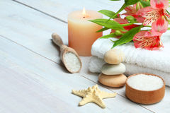 Spa accessory. Spa accessories: candle, sea salt and towel on wooden background Royalty Free Stock Image