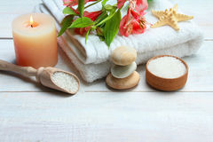 Spa accessory. Spa accessories: candle, sea salt and towel on wooden background Royalty Free Stock Photo