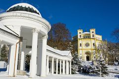 Spa architecture in winter - colonnade of mineral spring Karolina and catholic church - Marianske Lazne Marienbad Stock Photos