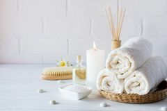 SPA aromatherapy background. Still life with white towel, bath oil, massage brush. And candle stock photos
