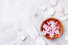 Spa, aromatherapy, beauty background with massage pebble, perfumed flowers water and candles on stone table from above. Relaxation and zen like concept. Flat Royalty Free Stock Images