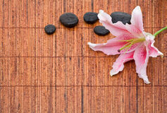 Spa arrangement with lily and stones. On bamboo mat Royalty Free Stock Image