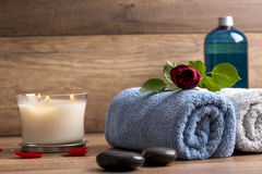 Spa arrangement. With two rolled towels, lit candle, black zen stones, moisturizing lotion  and red rose Stock Photos