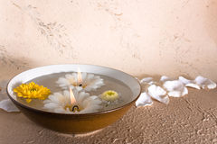 Spa atmosphere. Abowl with water and two candles in Royalty Free Stock Image