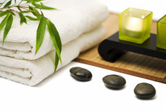 Spa background. Spa and wellness still-life with bamboo branch on towels, hot stones, candles, bamboo mat on white surface, soft focus Royalty Free Stock Image