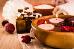 Spa background. Aromatherapy, spa items, candles, essential oils, sea salt, towels and flowers. Items for spa treatments. Candles, essential oils, water stock photos