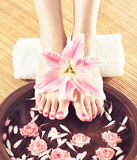Spa background with beautiful feet, flowers and petals. Legs, flowers, petals and a ceramic bowl. Spa, recreation and skin care concept Royalty Free Stock Photos
